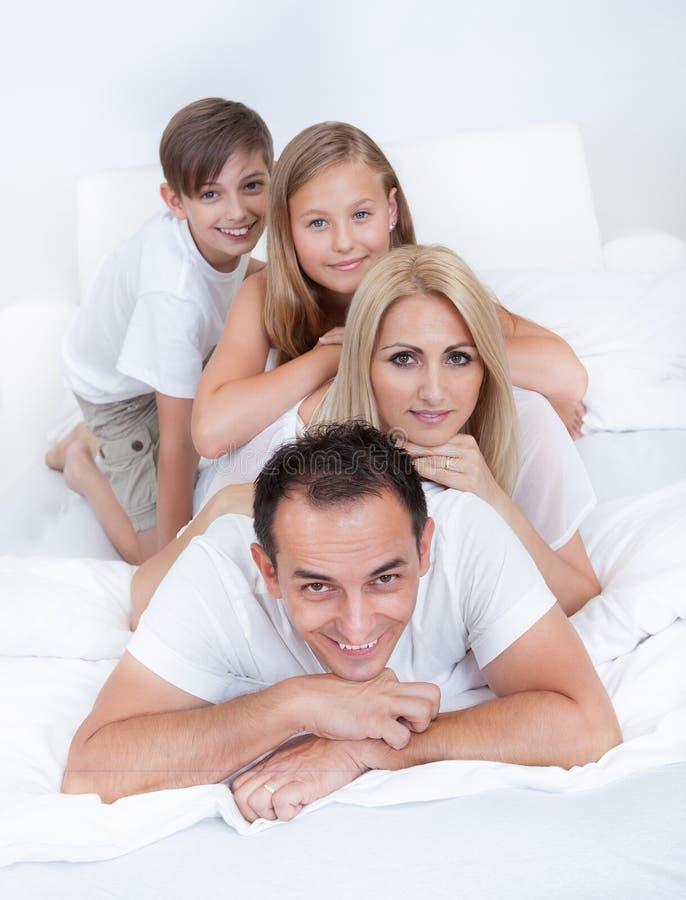 Lycklig familj med att ligga för två barn som överhopas på underlag royaltyfri bild