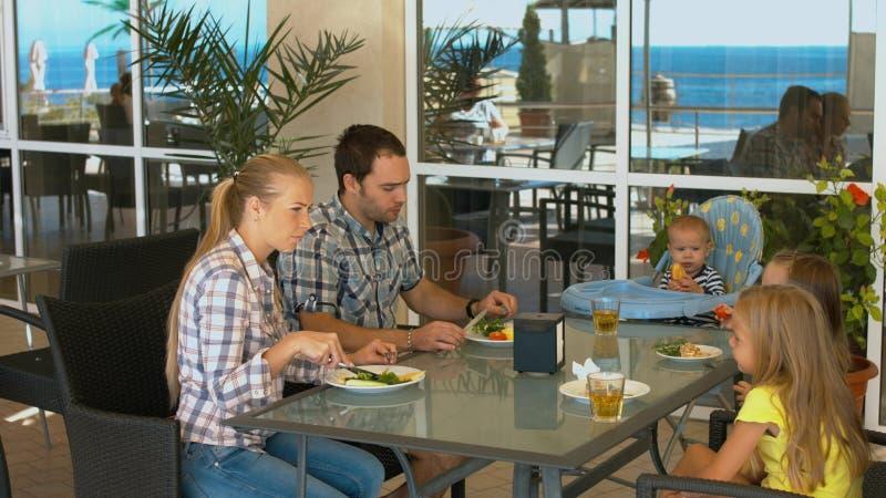 Lycklig familj med barn som har lunch i ett kafé royaltyfria foton