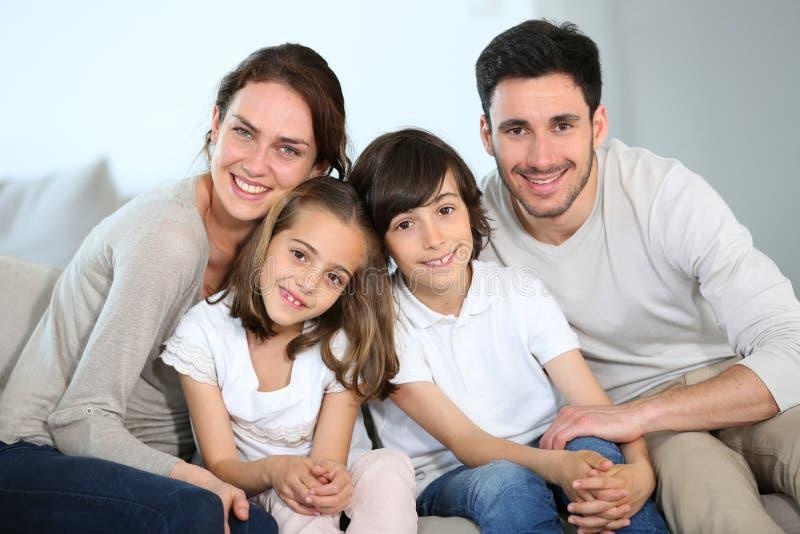 Lycklig familj med barn som sitter på soffan royaltyfria bilder