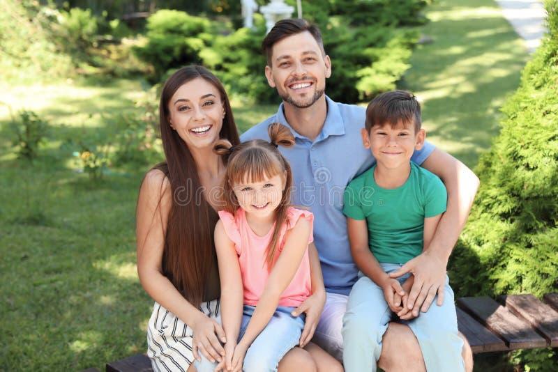 Lycklig familj med barn tillsammans på bänk royaltyfri fotografi