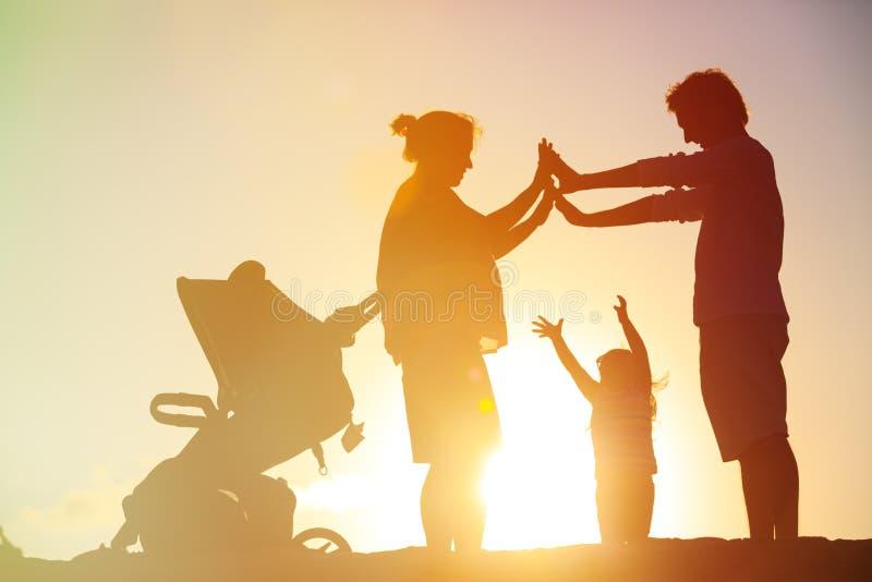 Lycklig familj med barnet och den gravida modern tillsammans på solnedgången arkivbilder