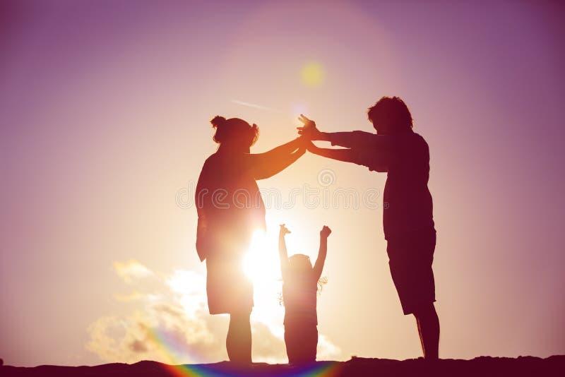 Lycklig familj med barnet och den gravida modern tillsammans på solnedgången arkivfoto