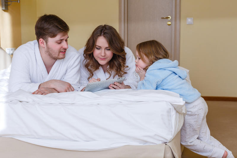 Lycklig familj med datorminnestavlan royaltyfri fotografi