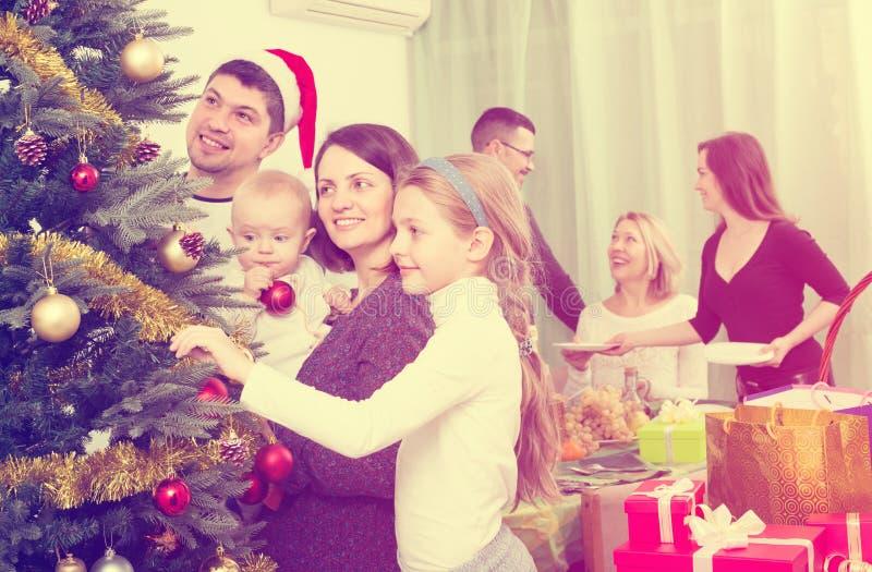 Lycklig familj med den hemmastadda julgranen arkivbilder