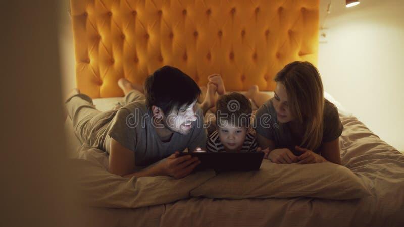 Lycklig familj med den lilla sonen ligga i säng som är hemmastadd och använda minnestavladatoren för hållande ögonen på tecknad f royaltyfri fotografi
