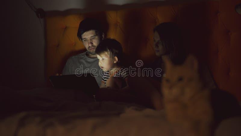Lycklig familj med den lilla sonen som lär att spela minnestavladatoren som ligger i säng med den hemmastadda katten royaltyfria bilder