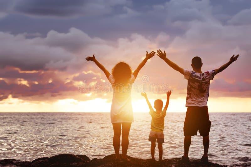 Lycklig familj med det sonhälsningssolnedgång och havet arkivbilder