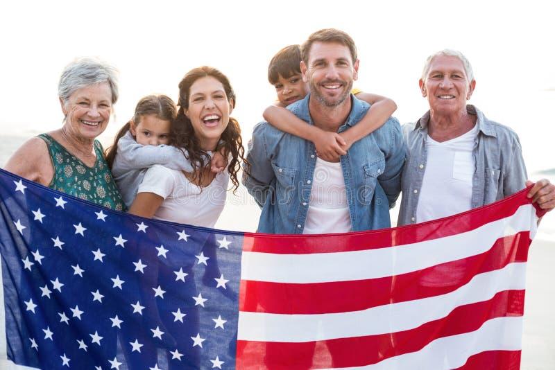 Lycklig familj med en amerikanska flaggan royaltyfri foto