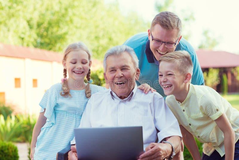 Lycklig familj med farfadern under internet som talar på bärbara datorn arkivbilder