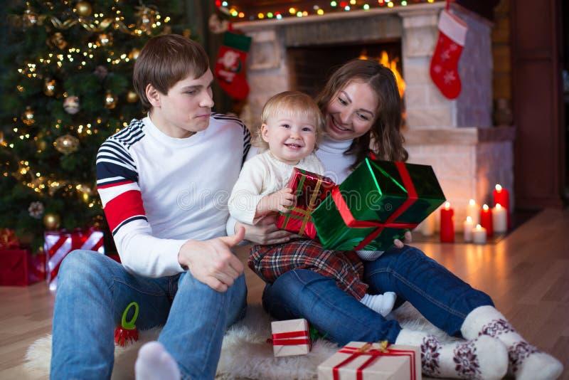 Lycklig familj med gåvor som sitter på julgranen arkivfoto