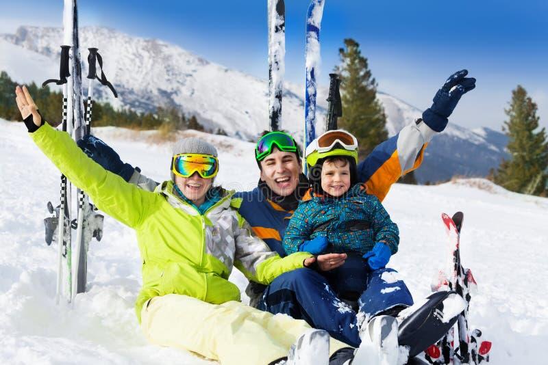 Lycklig familj med händer upp på snö, når att ha skidat royaltyfri foto