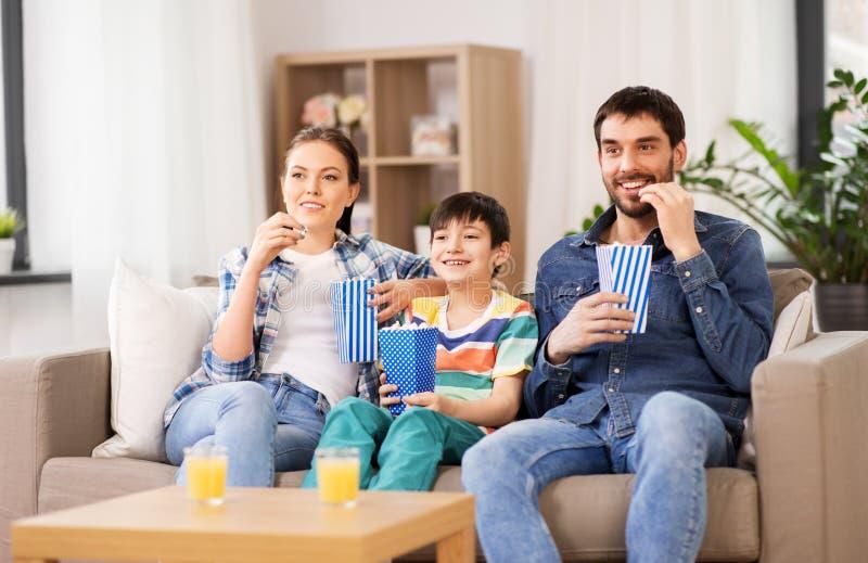 Lycklig familj med h?llande ?gonen p? tv f?r popcorn hemma arkivbild