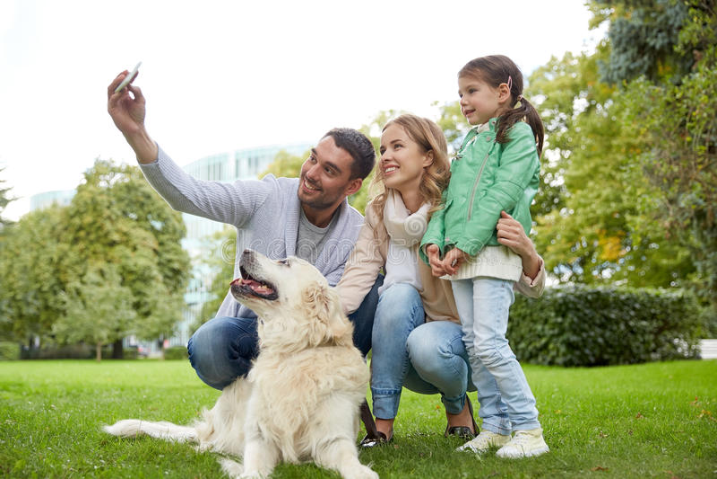 Lycklig familj med hunden som tar selfie vid smartphonen royaltyfri fotografi