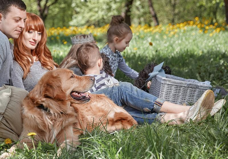 Lycklig familj med husdjuret på picknick i sommardag royaltyfri bild