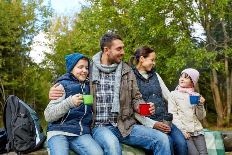 Lycklig familj med koppar som dricker varmt te på lägret royaltyfri fotografi