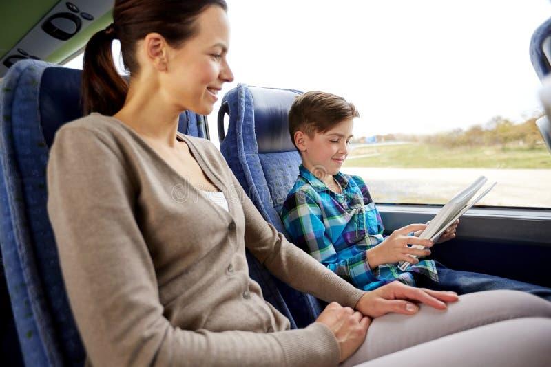 Lycklig familj med minnestavlaPC:n som sitter i loppbuss royaltyfria bilder