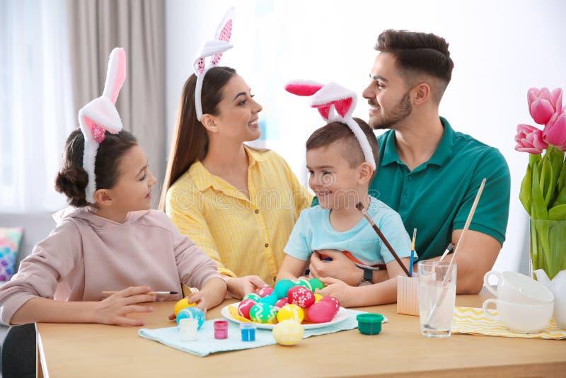 Lycklig familj med påskägg hemma royaltyfria bilder