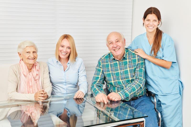 Lycklig familj med pensionärpar och sjuksköterska fotografering för bildbyråer