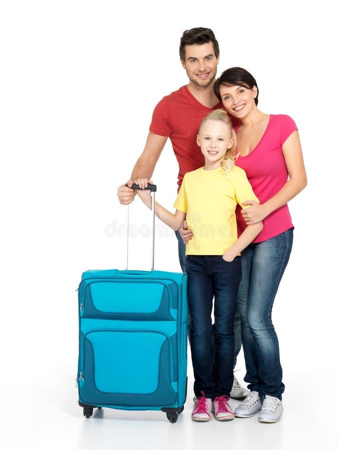 Lycklig familj med resväska på studion royaltyfria bilder