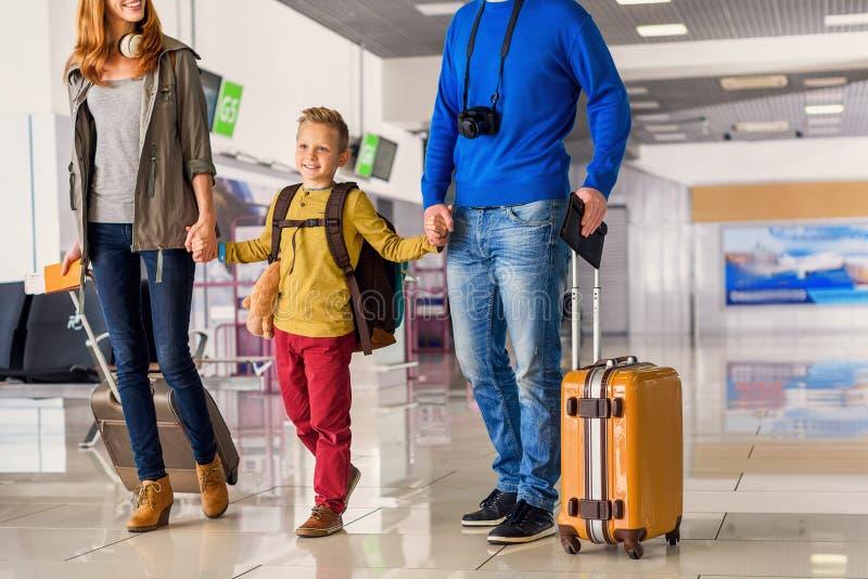 Lycklig familj med resväskor i flygplats arkivfoto