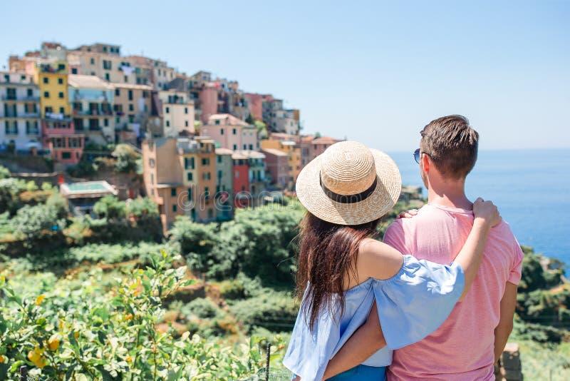 Lycklig familj med sikt av den gamla kuststadbakgrunden av Vernazza, Cinque Terre nationalpark, Liguria, Italien royaltyfri bild