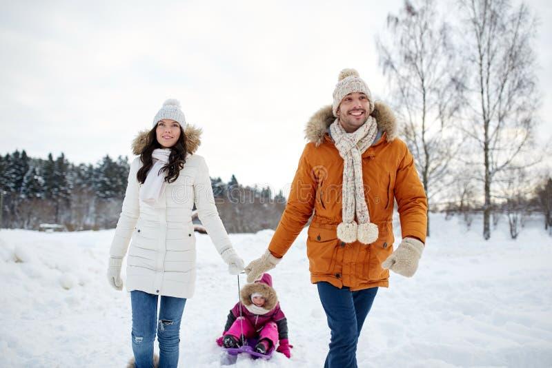 Lycklig familj med släden som utomhus går i vinter arkivbild