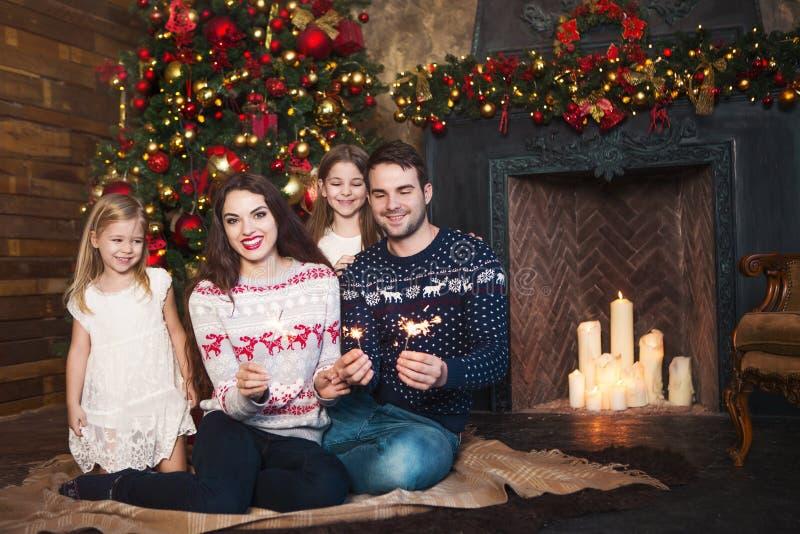 Lycklig familj med tomtebloss som firar jul arkivbild