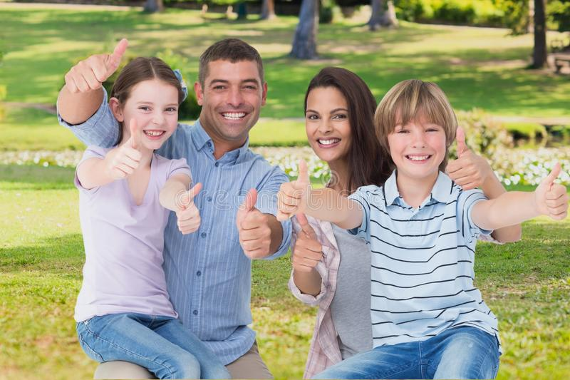 Lycklig familj med tummar upp på trädgård royaltyfria bilder