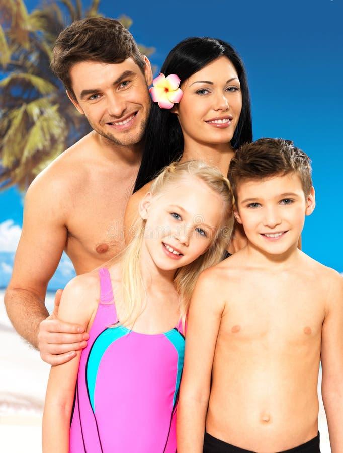 Lycklig familj med två barn på den tropiska stranden royaltyfri foto