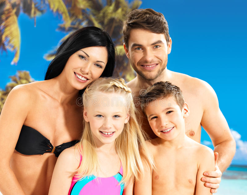 Lycklig familj med två barn på den tropiska stranden arkivbilder
