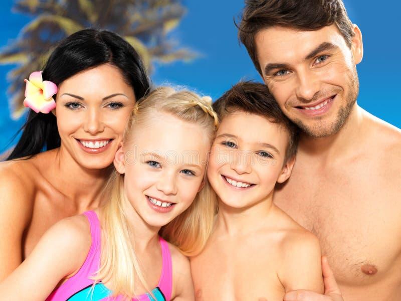 Lycklig familj med två barn på den tropiska stranden arkivfoto