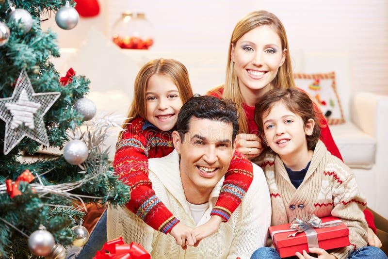 Lycklig familj med två ungar på jul fotografering för bildbyråer
