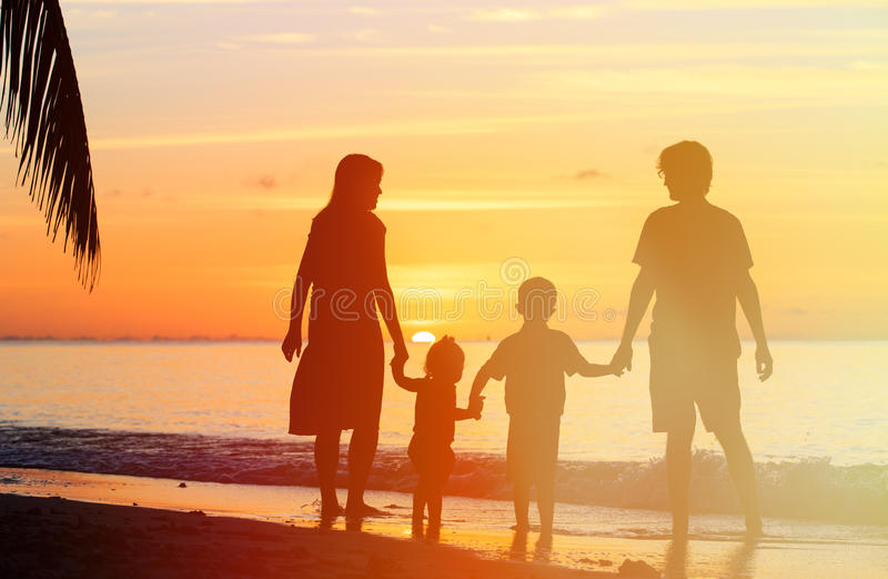 Lycklig familj med två ungar på solnedgångstranden royaltyfria foton