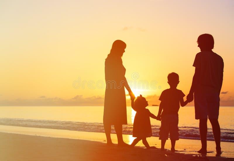 Lycklig familj med två ungar på solnedgångstranden arkivbild
