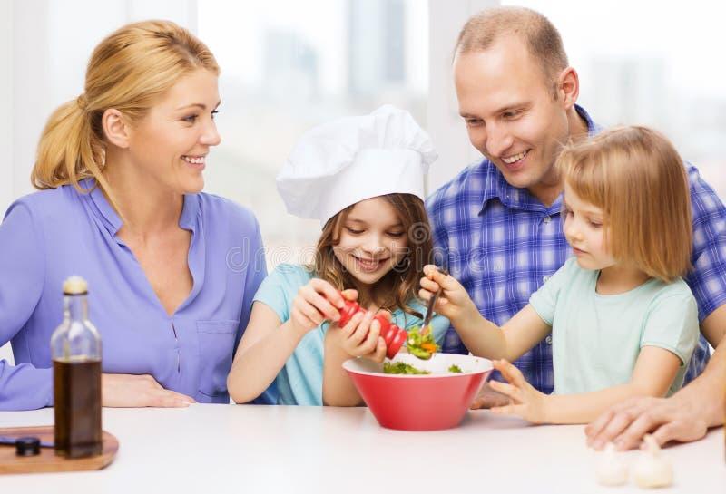 Lycklig familj med två ungar som gör matställen hemmastadd royaltyfria bilder