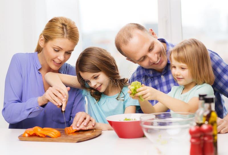 Lycklig familj med två ungar som gör matställen hemmastadd arkivbilder
