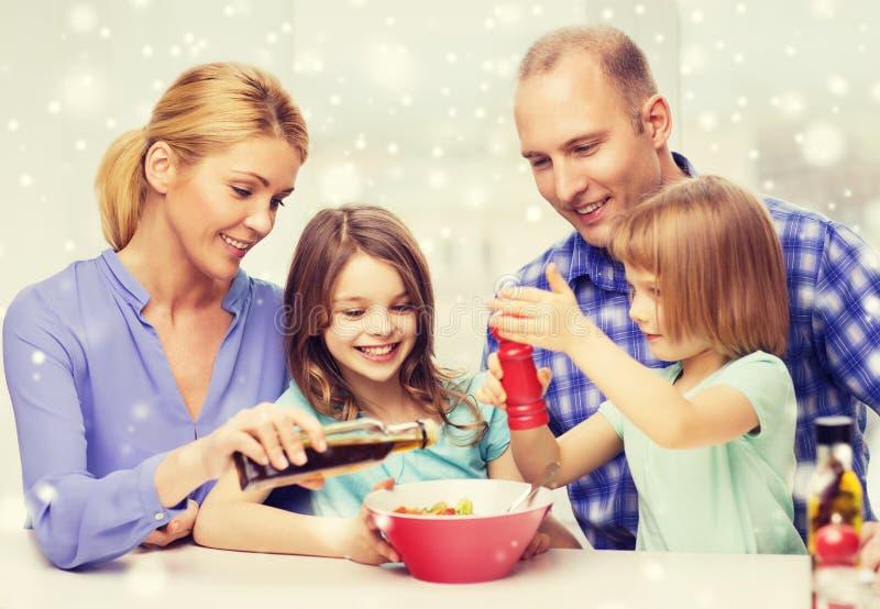 Lycklig familj med två ungar som gör sallad hemmastadd royaltyfri fotografi