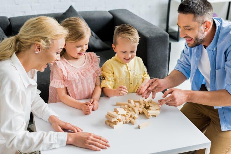 lycklig familj med två ungar som spelar med träkvarter arkivbilder