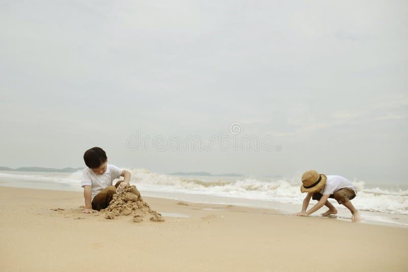 Lycklig familj med tv? ungar p? stranden arkivfoto