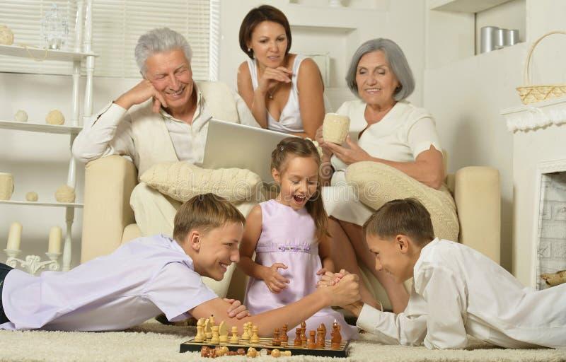 Lycklig familj med ungar med bärbara datorn royaltyfri bild
