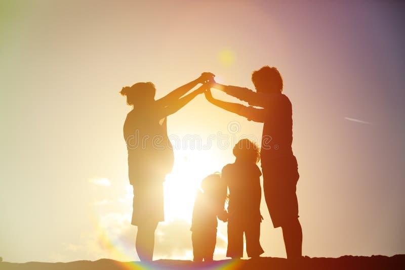 Lycklig familj med ungar och den gravida modern tillsammans på solnedgången royaltyfri bild