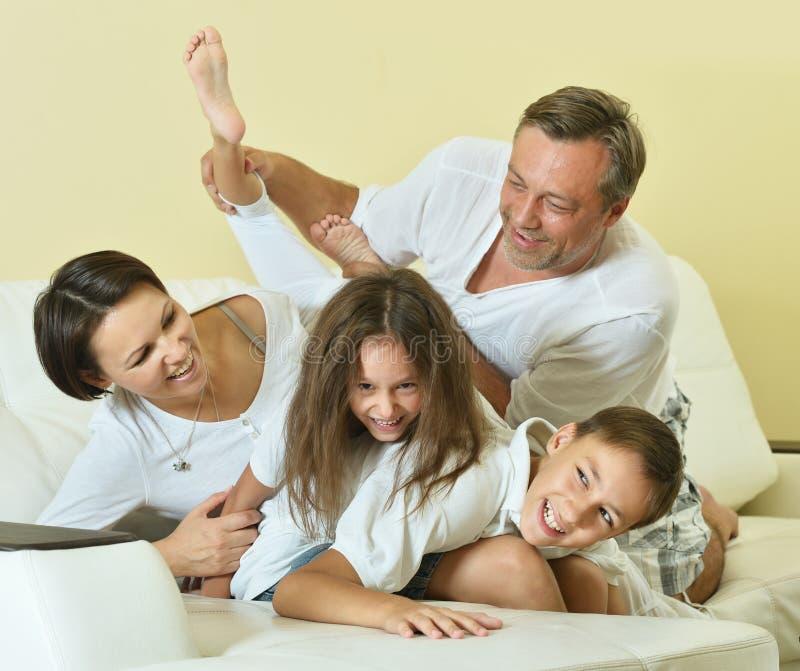 Lycklig familj med ungar på soffan arkivbilder