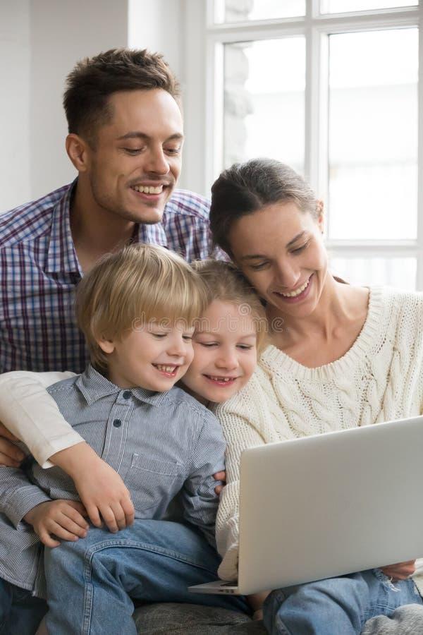 Lycklig familj med ungar som har den roliga användande bärbara datorn tillsammans, vertica royaltyfri fotografi