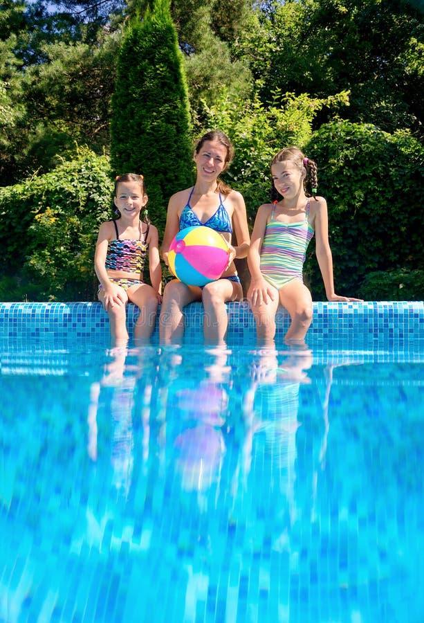 Lycklig familj med ungar som har gyckel i simbassäng på semester arkivfoto