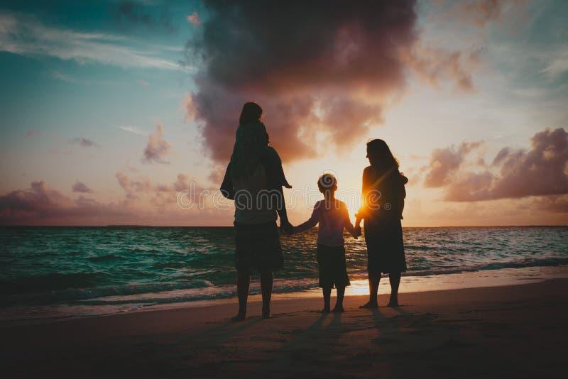 Lycklig familj med ungar som har gyckel på solnedgångstranden royaltyfria foton