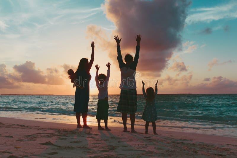 Lycklig familj med ungar som har gyckel på solnedgångstranden arkivbilder
