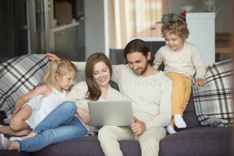 Lycklig familj med ungar som hemma använder bärbara datorn på soffan royaltyfri foto