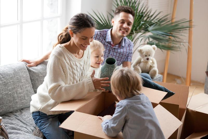 Lycklig familj med ungar som packar upp askar som flyttar sig in i nytt hem royaltyfri fotografi