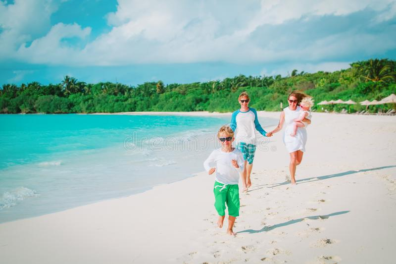 Lycklig familj med ungelek på strandsemester royaltyfri fotografi