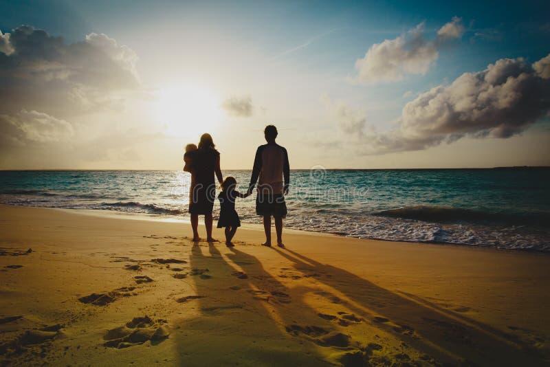 Lycklig familj med ungelek p? solnedg?ngstranden arkivfoto